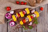 Sliced vegetables on wooden picks and bread on table close-up