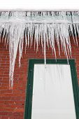 pic of framing a building  - Long delicate fingers of ice hang from a gutter atop a red brick building with a green framed window reflecting the ice and snow - JPG