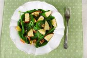 Green salad with spinach, apples, walnuts and cheese on color tablecloth background
