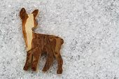 Wooden roe deer on snowy surface with copy space