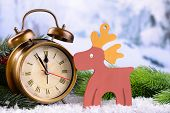 Alarm clock with Christmas decorations on light background