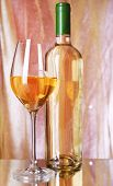 Wine bottle and wineglass with white wine on bright background