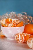 Sweet tangerines and oranges on table in bowl on Christmas lights background