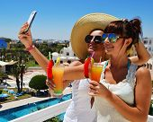 Two Young Women Taking Picture Of Themselves On Vacation