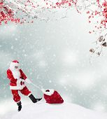 Santa Claus carrying gift sack on snowy hill. Free space for text