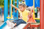 Cute small mixed race girl using a slide at a colorful playground