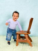 Adorable African baby boy trying to stand with help of a chair