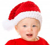 Cute Santa baby portrait, sweet little girl wearing red festive hat isolated on white background, celebrating Christmas time holidays