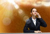 Young upset businesswoman talking on mobile phone