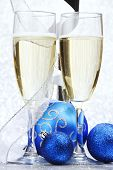 Glasses of champagne and decorative christmas balls on glitter background