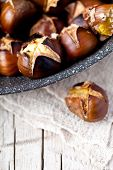 roasted chestnuts in a pan on wooden background
