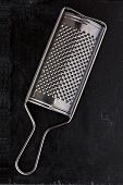 metal grater over blackboard background