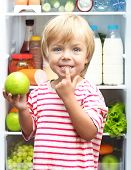 Happy little boy with green apple showing his teeth against refrigerator with food
