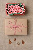 High angle shot of a bowl full of mini candy canes, a plain paper wrapped Christmas present and tree and star antique decorations on a burlap surface. Vertical Format.