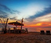Wooden chairs and umbrellas on white beach in sunset time at Phu Quoc island in Vietnam