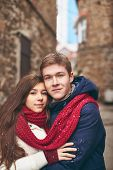 Portrait of attractive young man and his charming girlfriend looking at camera outdoors