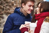 Portrait of affectionate young dates having coffee from plastic glasses outside