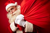 Portrait of Santa Claus with huge and heavy red sack looking at camera