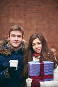 Portrait of young dates with giftbox and plastic glass of coffee looking at camera outdoors