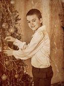 Happy child decorate on Christmas tree.