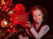Child with gift box near Christmas tree with glowing  lights.