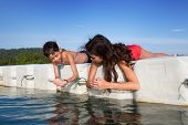Young boy showing his sister tiny prawns he caught while they were on floating platform on tropical island