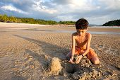 Young boy having fun outdoors playing in the sand by the beach at sunset