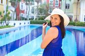 Beautiful woman in blue dress and white hat smiling by the swimming pool
