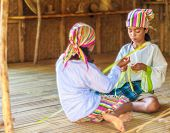 two young beautiful child girls in traditional clothes in bamboo house making toys from palm leaves, Philippines, Malay, Panay