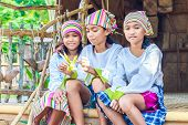 pic of bamboo leaves  - three young beautiful child girls in traditional clothes in bamboo house making toys from palm leaves - JPG