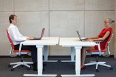 stock photo of workstation  - business man and woman in correct sitting posture at workstations in the office - JPG