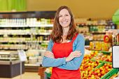 Portrait of smiling female store manager in a supermarket with her arms crossed