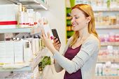 Youn woman comparing prices with her smartphone in drugstore department of a supermarket