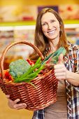 Smiling elderly woman with vegetable basket holding her thumbs up