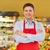 Portrait of happy retail salesman in a supermarket