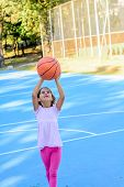 Seven year old girl  playing basketball