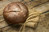 Loaf Of Rye Bread With Wheat Ears On Wood Background