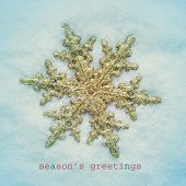 a golden snowflake-shaped christmas star on the snow and the sentence seasons greetings, with a retro effect