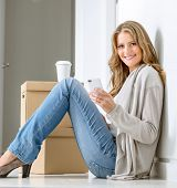 Smiling woman sitting on the floor with a pile of boxes, having a coffee break and texting with her smart phone