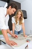 Man and woman looking at unrolled blueprints