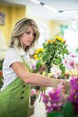 Portrait of a young florist arranging flowers