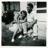CANADA - CIRCA 1940s: An antique photo shows  portrait of a a young married couple in front of their home.