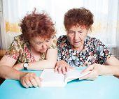 Two seniors. Old woman reading book. Friendship elderly