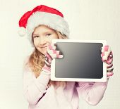 Child in christmas hat with tablet. Girl with pc