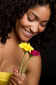 image of black curly hair  - Beautiful smiling young black woman smelling flowers - JPG