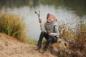 Cute happy child girl in knitted hat and sweater playing on river side