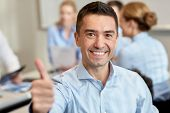 business, people and teamwork concept - smiling businessman showing thumbs up with group of businesspeople meeting in office