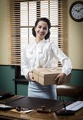 image of 1950s style  - Smiling secretary holding a mail package with rope and label 1950s style - JPG