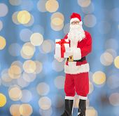 christmas, holidays and people concept - man in costume of santa claus with gift box over blue lights background
