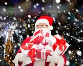 christmas, holidays and people concept - man in costume of santa claus with gift boxes over snowy night city background